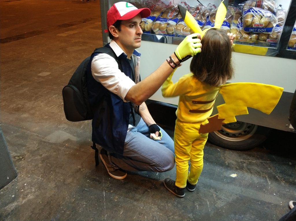 Padre cazador Pokémon arreglando las orejas a una pequeña Pikachu