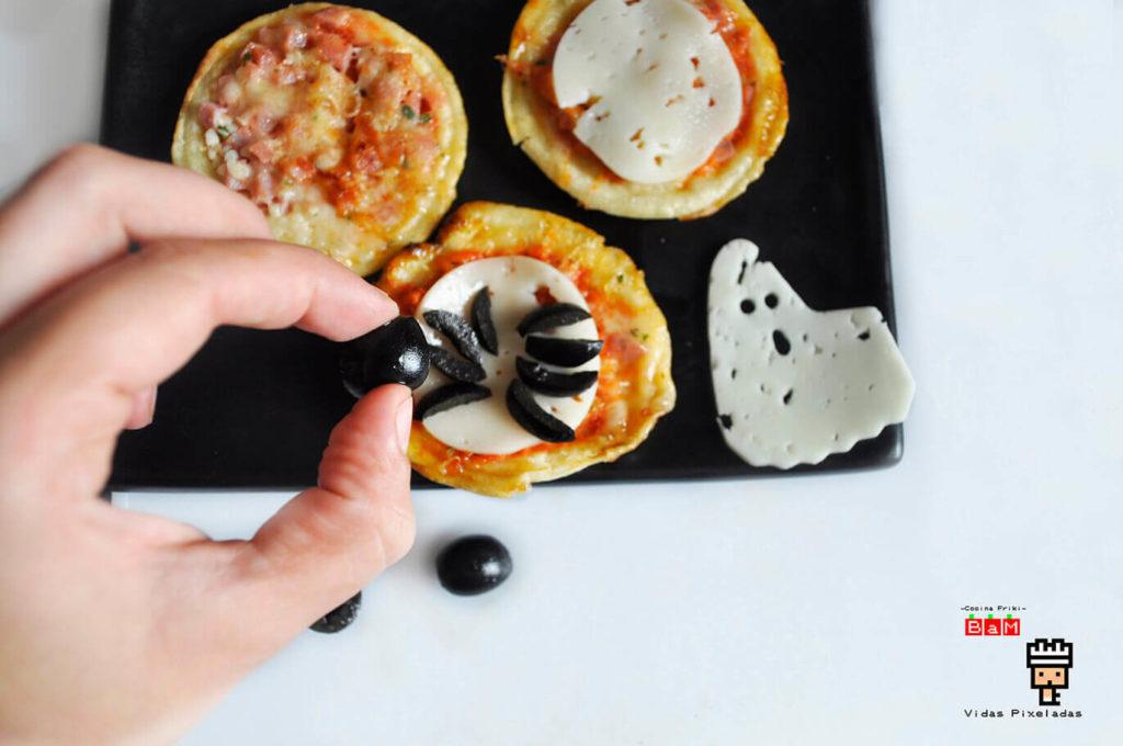 Decorar pizza de arañas con aceitunas