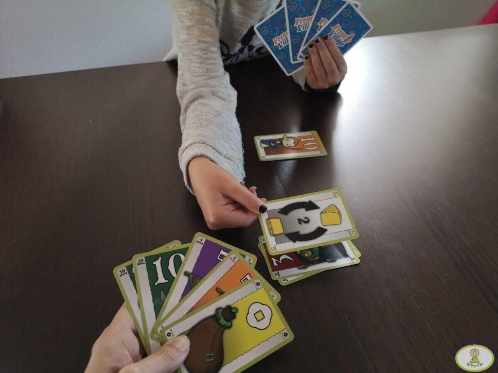 un jugador echa una carta de acción sobre la pila de descartes de otro jugador