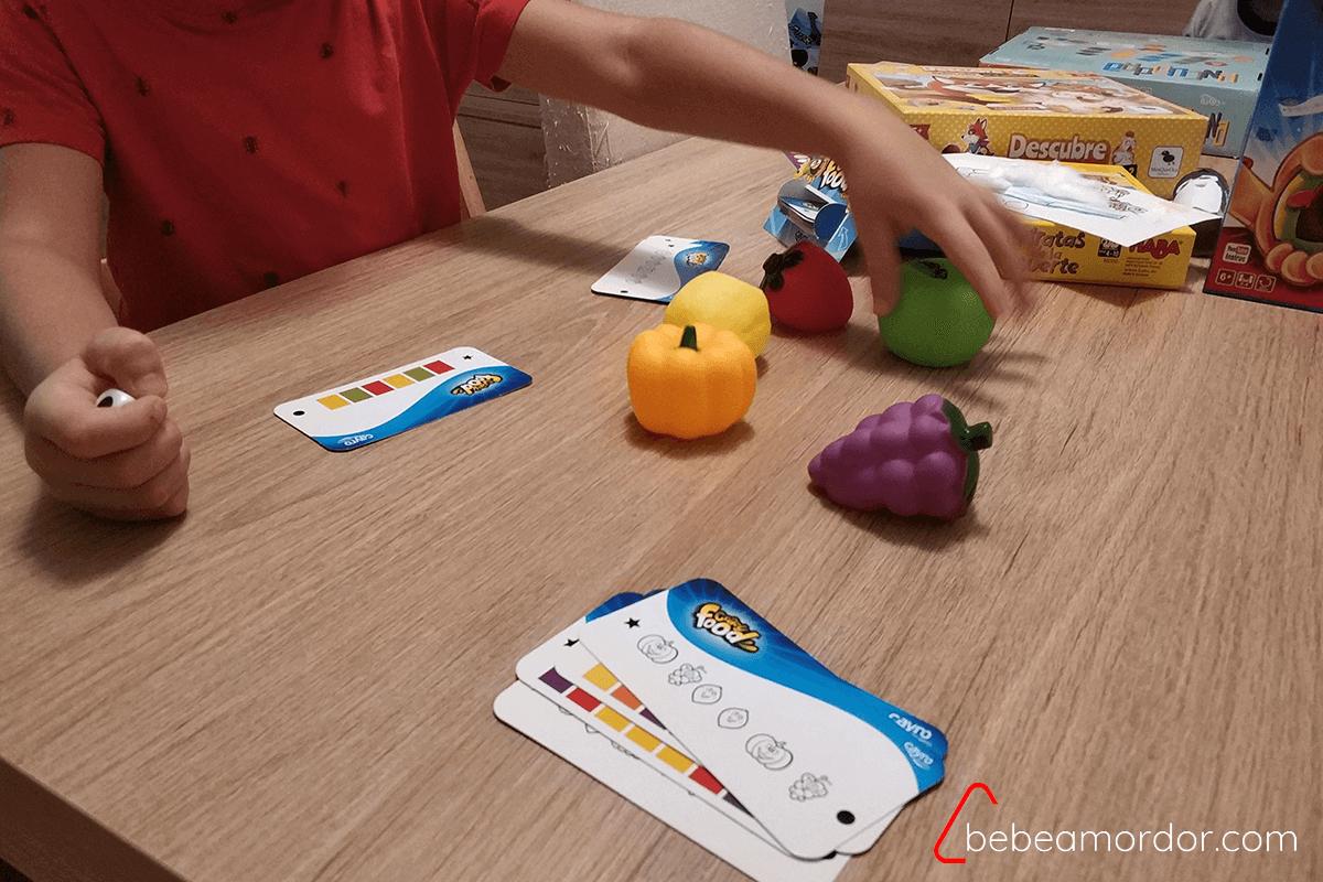 niño jugando al juego cogiendo una fruta (manzana verde)
