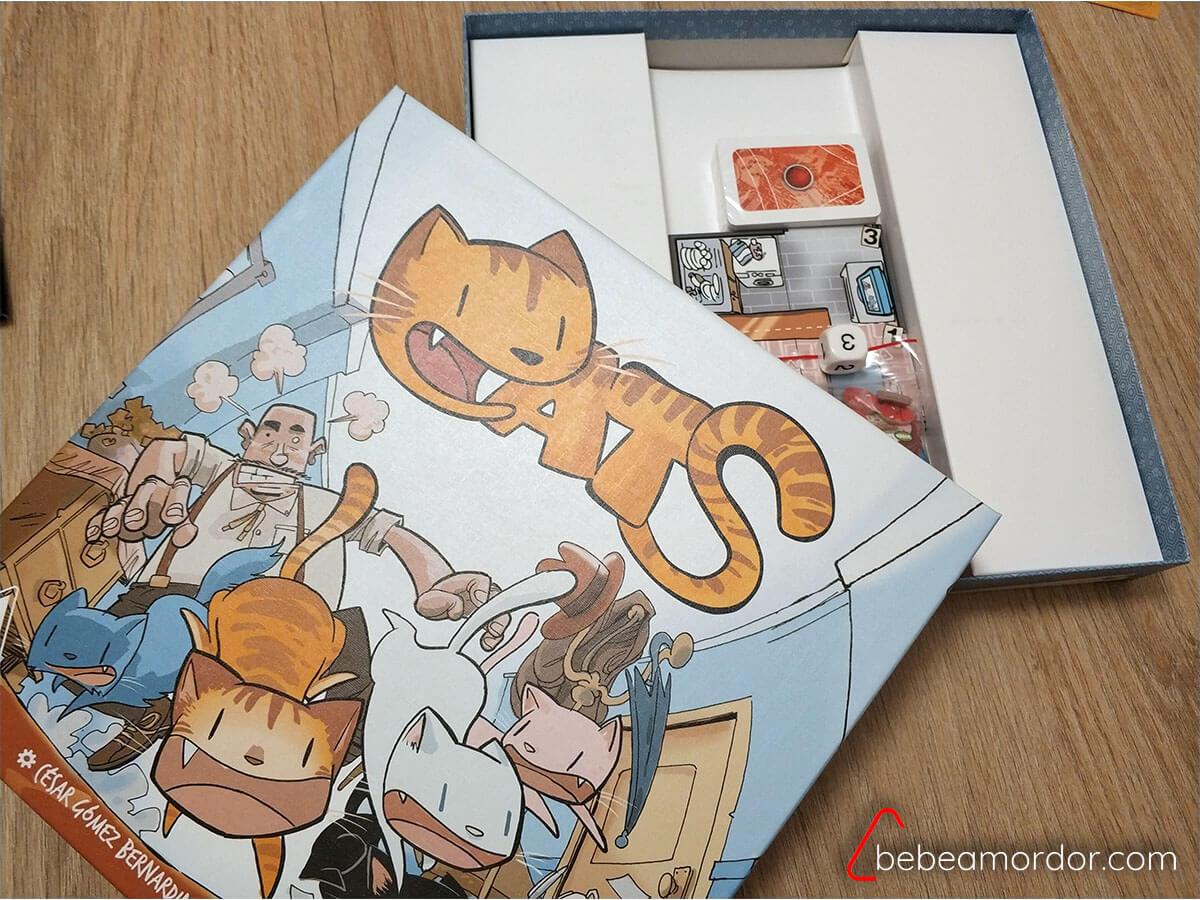 Caja del juego de mesa Cats abierta con componentes dentro.