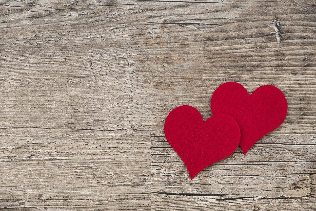 madera de fondo con dos corazones rojos de fieltro.