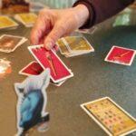 mano de mujer de más de 80 años jugando a juego de mesa Tranjiscolocar carta en montón