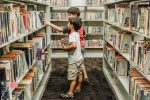 two-children-in-a-library-picking-books-on-the-shelves_t20_mRnQNn