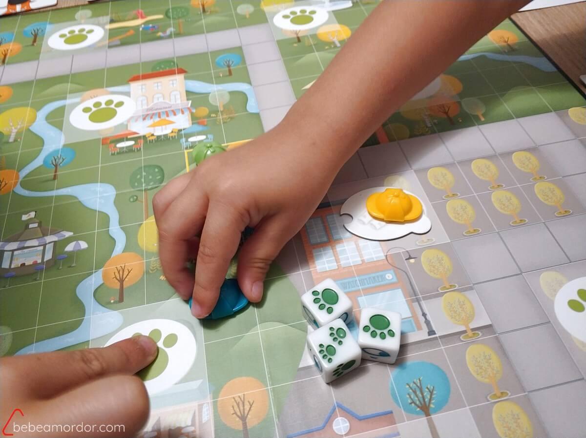 Una mano de niño pequeño cogiendo el gorro azul y movéndolo hacia una casilla de huella